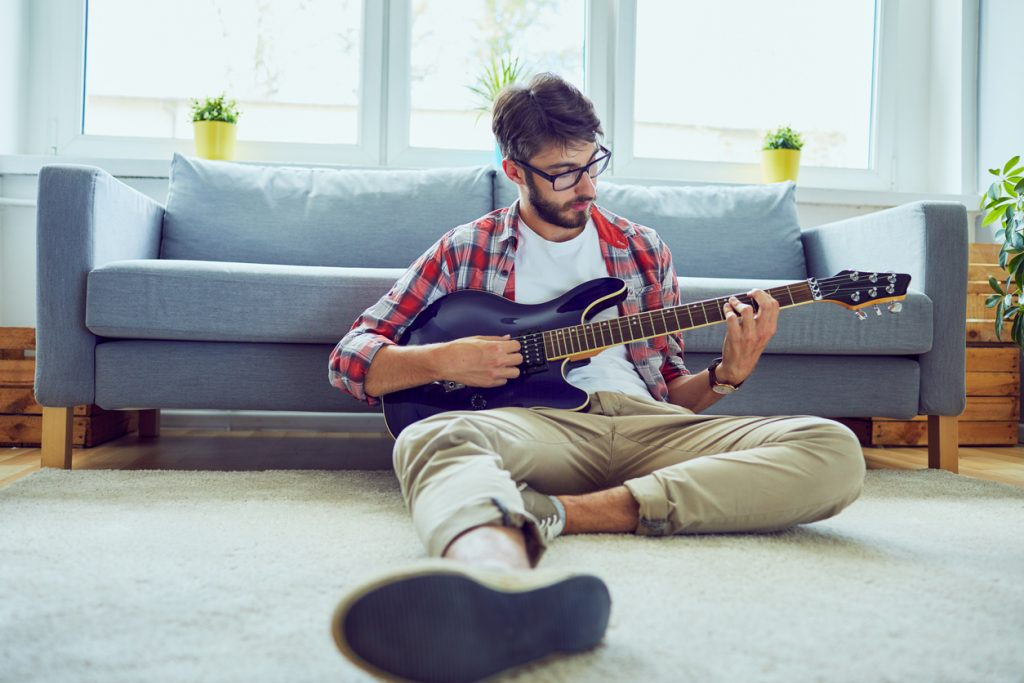 young man practicing guitar while stretching his fingers and sitting in living room