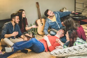 happy friends having party while listening to music and playing guitar